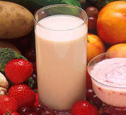 glass of milk surrounded by fruits and vegetables